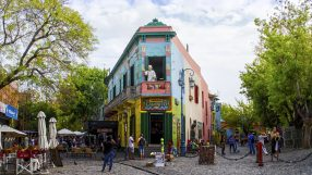 Buenos Aires, Argentina - April 15, 2015: The main square on of the Camanito in the La Boca neighborhood of Buenos Aires features brightly colored buildings and cobblestone streets that are a popular tourist destination. Tourists can be seen surrounding the most recognizable building the the neighborhood at the center of the square. The area is a popular destination for watching tango dancers in the street, shopping for souvenirs handicrafts made by local artisans and restaurants. It is the oldest neighborhood in Buenos Aires and is located at the mouth of the port, which gives it its namesake.