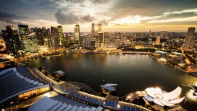 Aerial view of Singapore's Marina Bay with the beautiful Skyline illuminated at sunset. Backlit shot with wide-angle lens used for a greater panoramic impression.