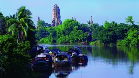 Ancient ruins at Ayutthaya, Thailand, with rice barges in foreground