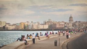 The Malecón, Old Havana, Cuba, with local Cuban residents and visitors relaxing and walking afternoon promenades. Featuring a broad esplanade, roadway, and seawall, the Avenida de Maceo is a famous place and tourist destination. People travel to view the Caribbean Sea waterfront, national capital city urban skyline, and community culture.