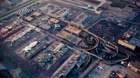 Los Angeles International Airport (LAX) stays busy under a setting sun as nighttime lights start to turn on.