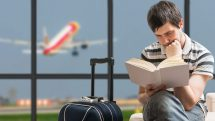 Man reading book at airport (iStock)